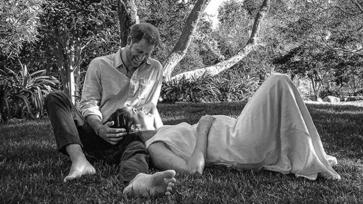 Meghan Markle y el príncipe Harry recostados en el césped anunciando su segundo embarazo