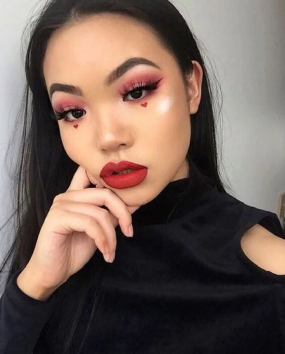 Valentine-inspired makeup in red and guina colors with hearts under the eyes