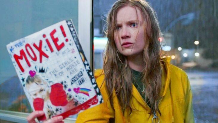 chica bajo la lluvia sosteniendo una libreta con apuntes; escena de la película Moxie