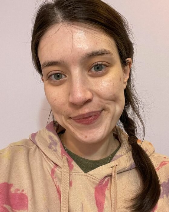 Chica de piel blanca, ojos azules y cabello largo castaño sujetado en una trenza se toma selfie sin maquillaje