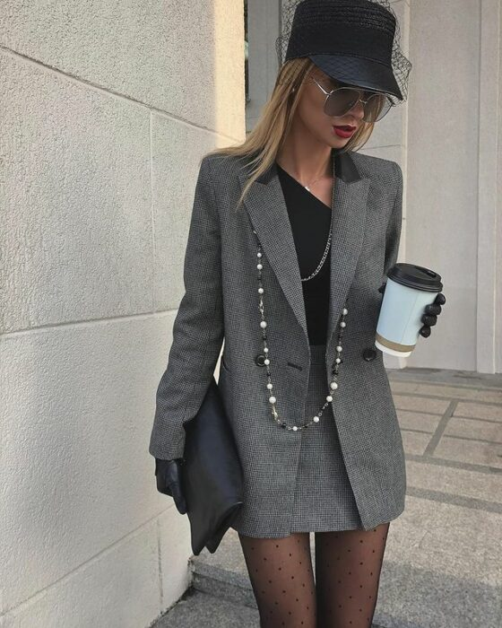 Victoria Fox wearing stockings, with gray mini skirt and blazer, black blouse, with bag and hat of the same color