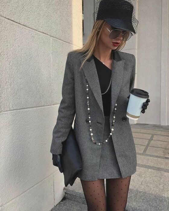 Victoria Fox usando medias, con mini falda y blazer color gris, blusa negra, con bolsa y sombrero del mismo color