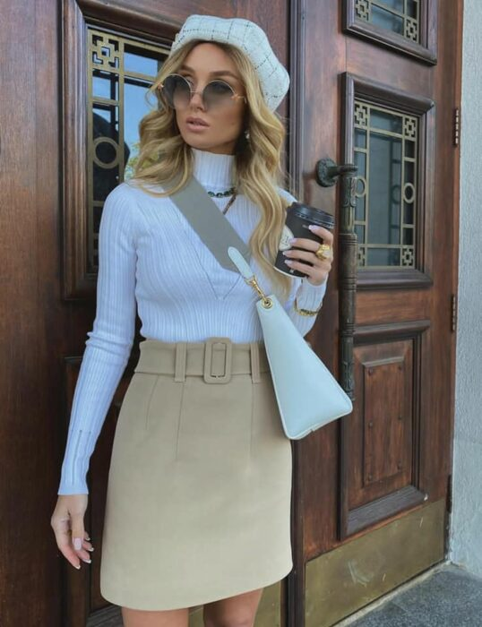Victoria Fox wearing beige mini skirt with white blouse and beret and handbag of the same color