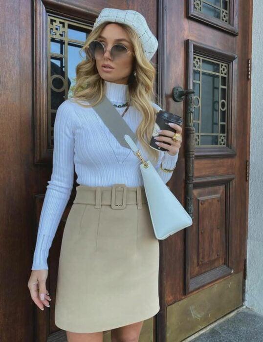 Victoria Fox usando mini falda color beige con blusa blanca y boina y bolsa de mano del mismo color