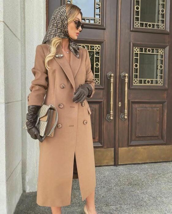 Victoria Fox usando un  abrigo color camel, pañuelo sobre la cabeza