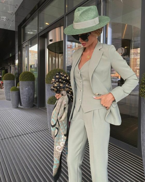 Victoria Fox wearing a green tailored suit with pants, vest and jacket, with a hat of the same color