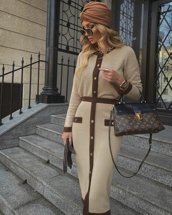 Victoria Fox usando un vestdo de manga larga y botones de color beige con detalles cafés