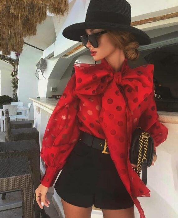 Victoria Fox usando short color negro y sombrero del mismo tono, y blusa color rojo