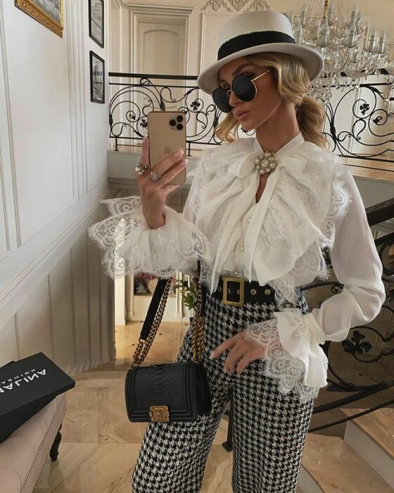 Victoria Fox wearing black and white checked trousers, with a white embroidered blouse, a hat of the same color, a black handbag