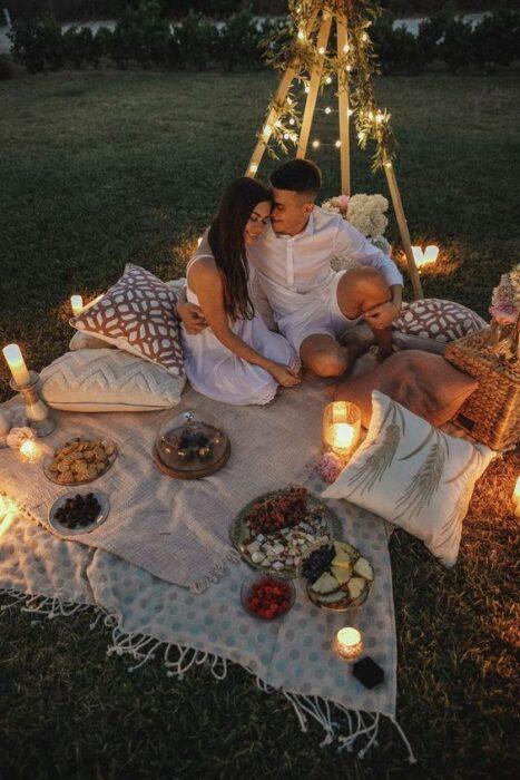 Pareja en una cita romántica de noche tipo picnic