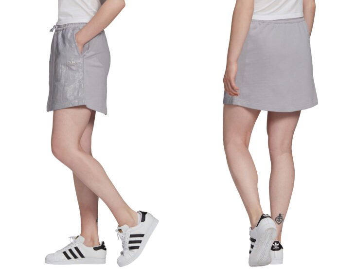 Comfortable clothing and fashion for women; girl with gray sports skirt with bags on the sides, with white Adidas sports shoes with black stripes