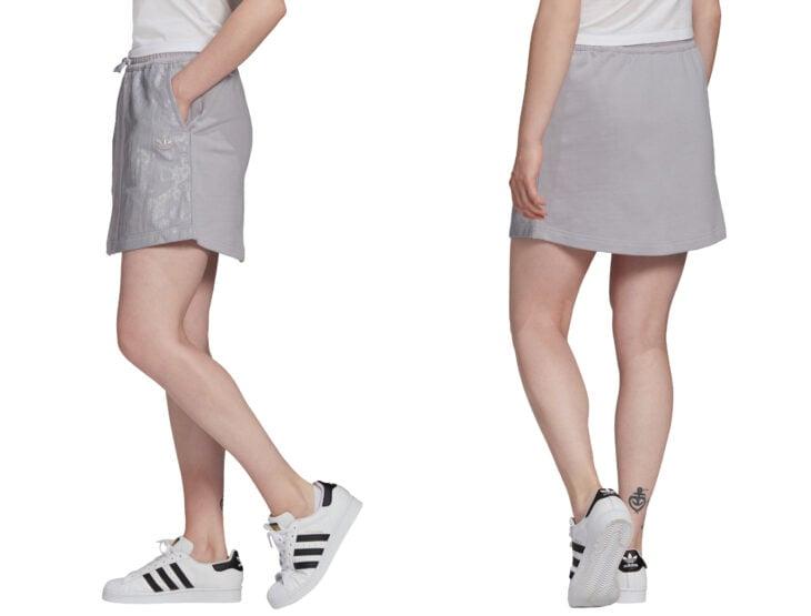 Ropa y moda cómoda para mujeres; chica con falda deportiva gris con bolsas a los costados, con tenis deportivos Adidas color blanco con franjas negras