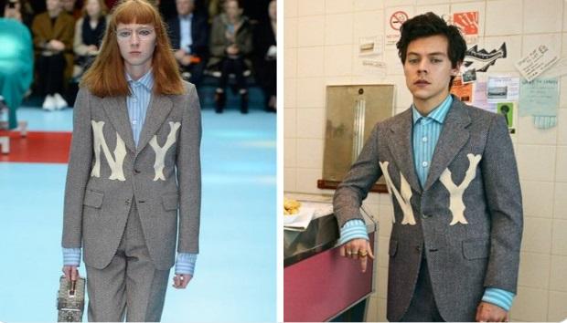 Harry Styles vistiendo una camisa azul cielo con rayas blancas y encima un saco gris con letras en blanco que dicen NY