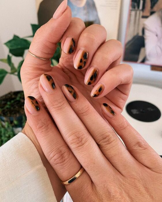 Manicure with tortoiseshell design on one half and nude on the other