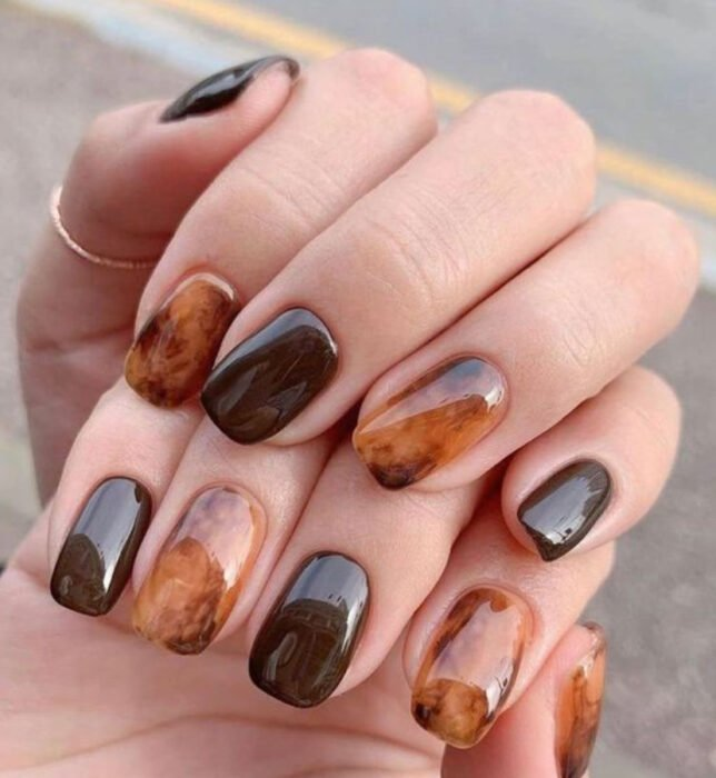 Tortoiseshell style manicure on several fingers with the rest in a brown tone