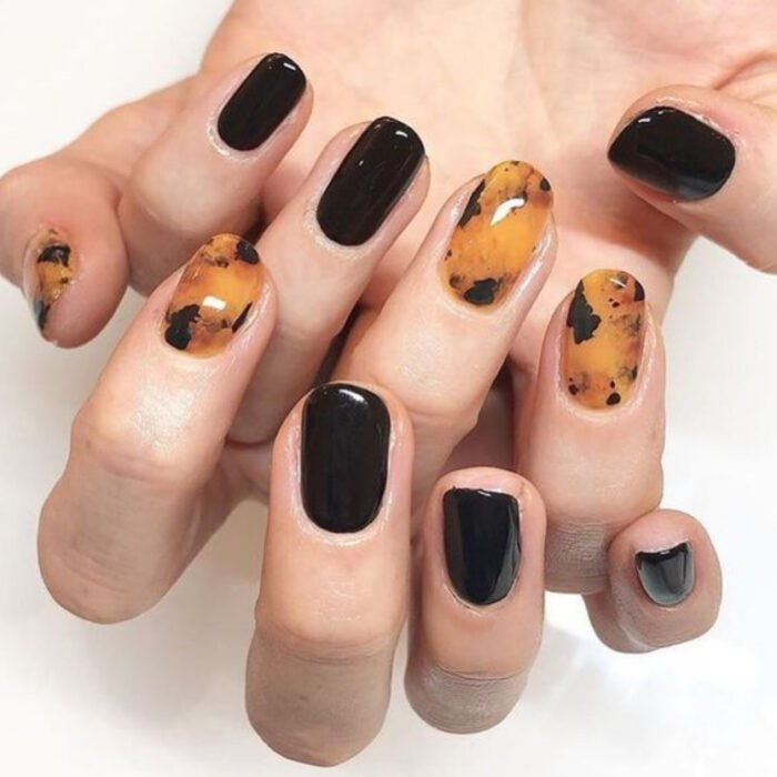 Manicure with tortoiseshell design on several fingers and black enamel on the rest