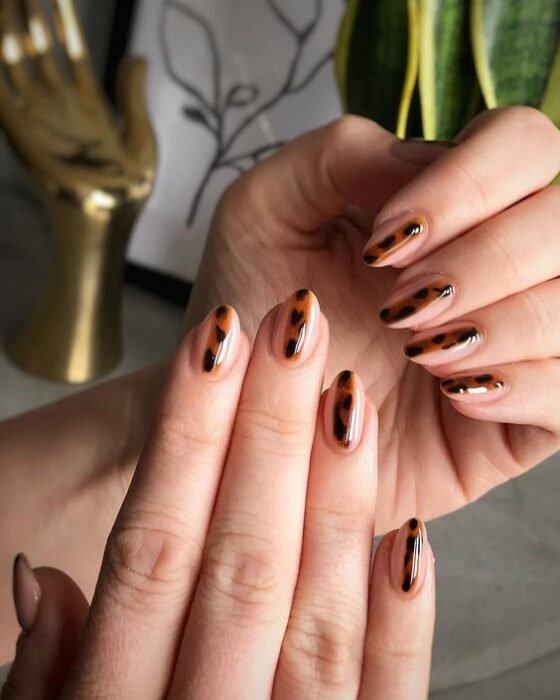 Manicure with a nude base and a line in the middle with a tortoiseshell print