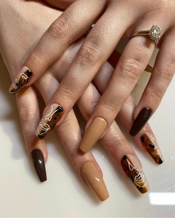 Tortoiseshell style manicure on several fingers with the rest in nude tone
