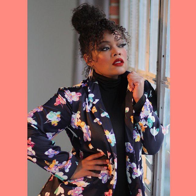 Yvette Nicole Brown posando recargada en una ventana vistiendo una blusa negra de cuello alto con una saco floreado