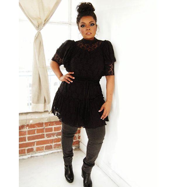 Yvette Nicole Brown posando de pie con una blusa larga negra. pantalón gris y botines negros altos
