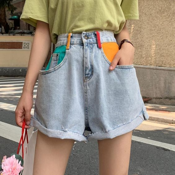 girl wearing short shorts with bags painted in yellow and green