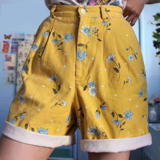 girl wearing short shorts painted with blue daisies