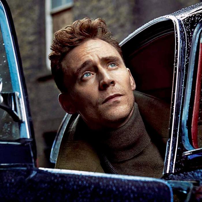 tom hiddleston rubio con suéter café de cuello alto y chamarra café