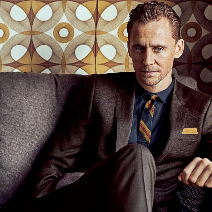 tom hiddleston con traje café oscuro, camisa azul de vestir y corbata azul con amarillo oscuro