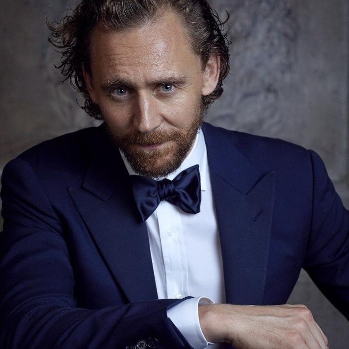 tom hiddleston con traje azul, corbatín de moño azul y camisa de vestir blanco