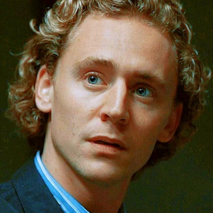 tom hiddleston rubio con camisa azul y abrigo azul marino