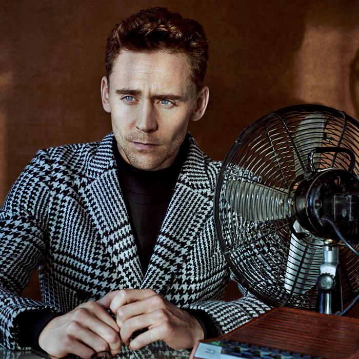 tom hiddleston con camiseta negra de manga larga y abrigo saco gris de cuadros