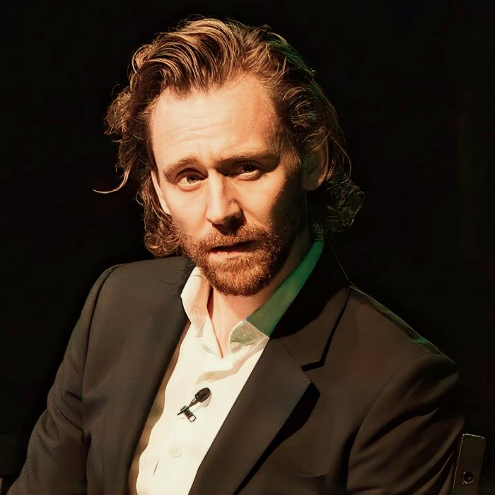 tom hiddleston con cabello largo, barba, camisa blanca y saco negro