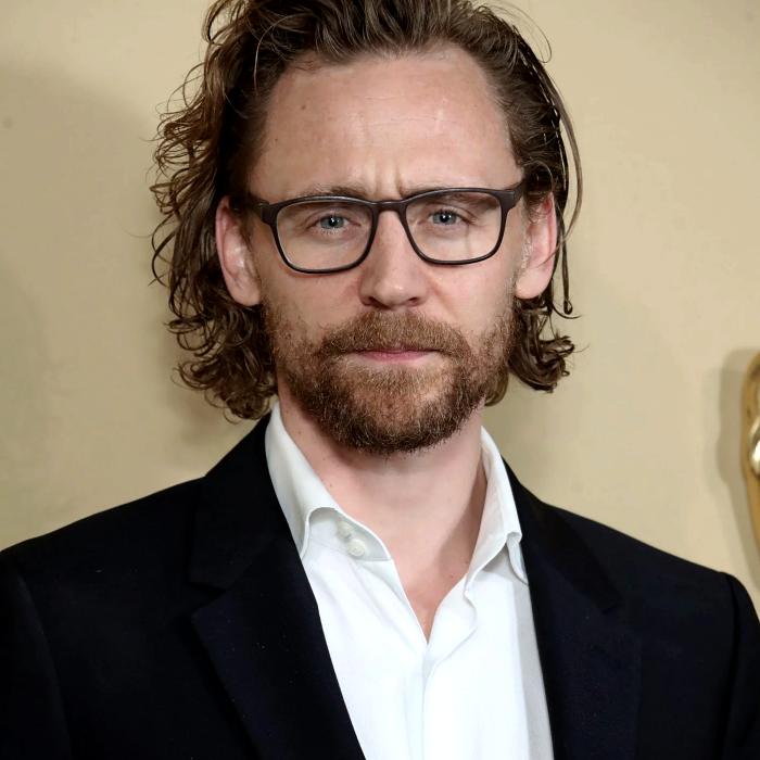 tom hiddleston con lentes, camisa blanca, saco negro