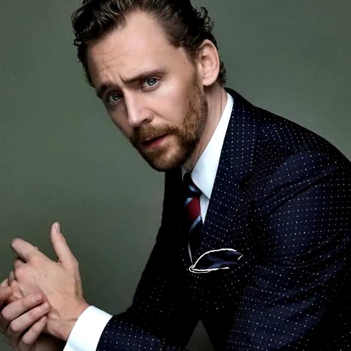 tom hiddleston con traje azul, camisa blanca de vestir y corbata roja