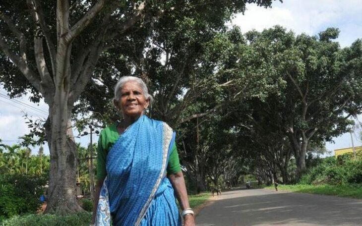 Saalumarada Thimmakka caminando por la carretera con árboles a los lados