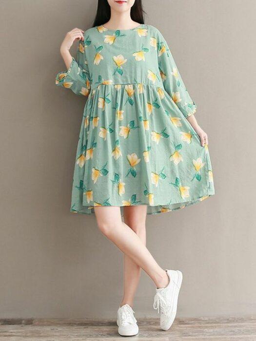Chica usando vestido floreado color verde con estampado amarillo y tenis blancos