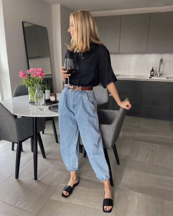 Chica usando playera negra, con mom jeans de mezclilla clara y sandalias de color negro