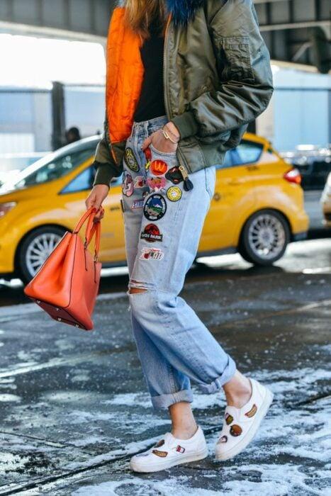 chica llevando jeans rotos con parches decorativos; ; 13 Maneras de salvar tus jeans rotos y seguir a la moda