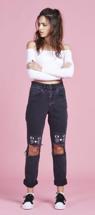 chica con jeans rotos pitandos con la cara de un gatito; ; 13 Maneras de salvar tus jeans rotos y seguir a la moda