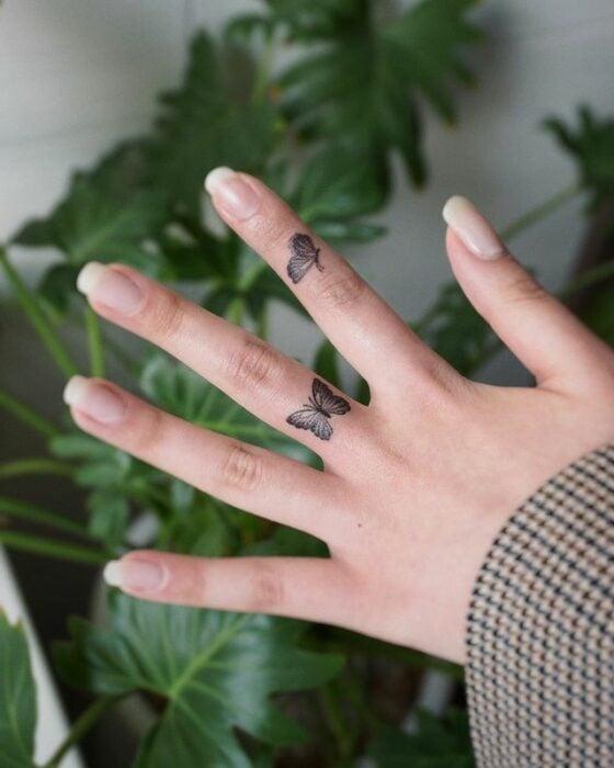 Chica mostrando sus tatuajes de mariposa como anillos;  15 Bellos tatuajes con mariposas para iniciar una metamorfosis