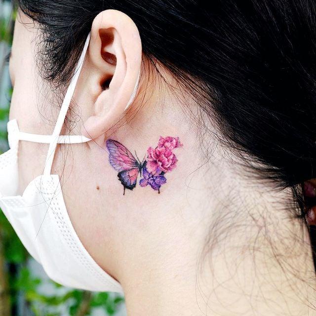 Tatuaje de mariposa detrás del oido en tonos rosas con flores desprendidas;  15 Bellos tatuajes con mariposas para iniciar una metamorfosis
