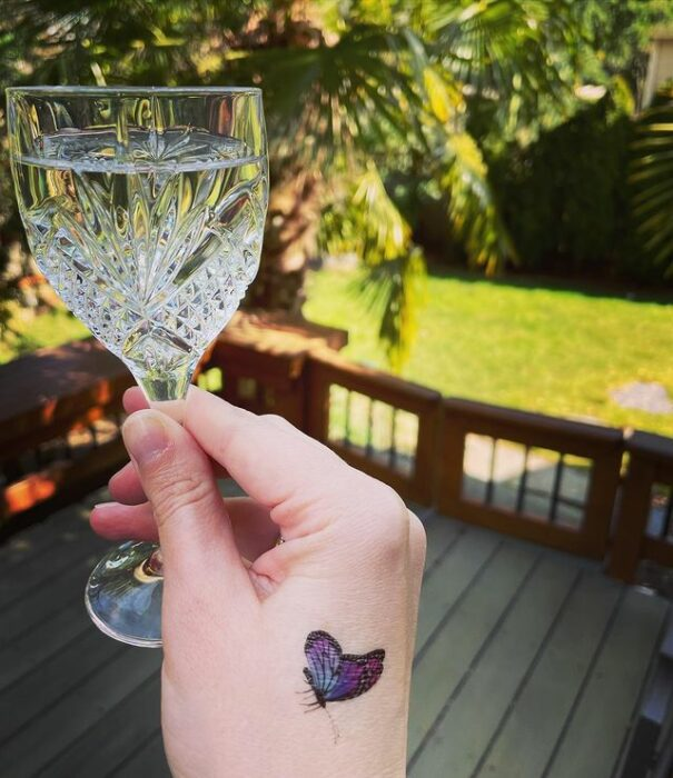 Minitatuaje de mariposa en la mano en tonos morado y rosa;  15 Bellos tatuajes con mariposas para iniciar una metamorfosis