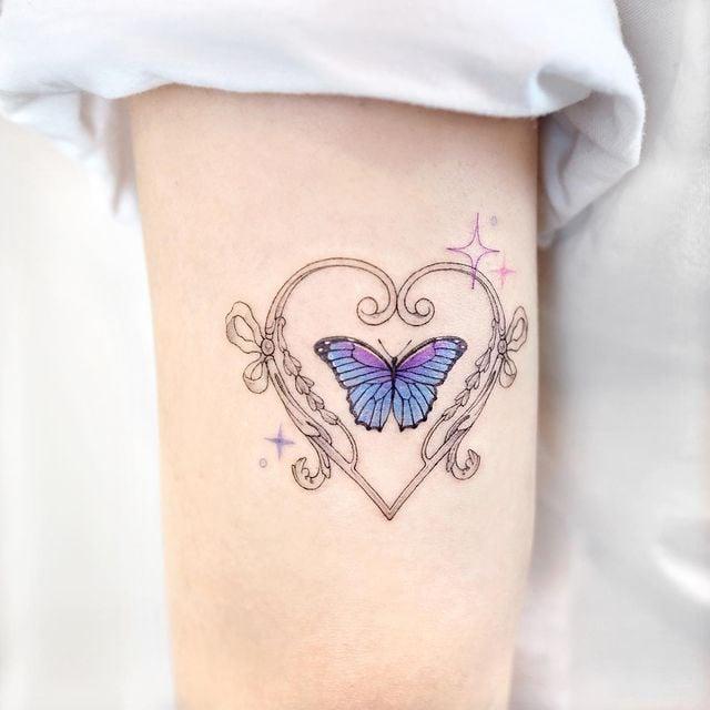 Tatuaje de mariposa en tonos morados rodeado por un corazón;  15 Bellos tatuajes con mariposas para iniciar una metamorfosis