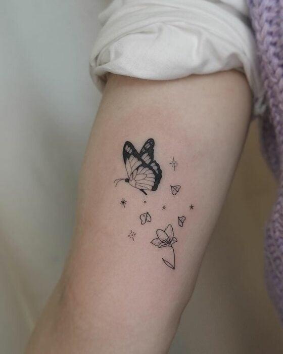 Minitatuaje de mariposa en color negro sobrevolando unas flores;  15 Bellos tatuajes con mariposas para iniciar una metamorfosis