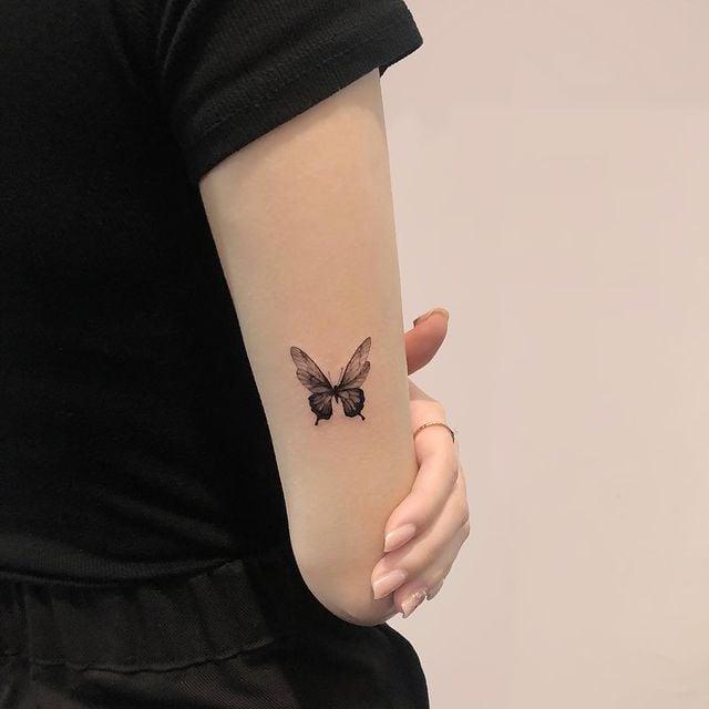 chica mostrando un tatuaje de mariposa en el coda en tono negro;  15 Bellos tatuajes con mariposas para iniciar una metamorfosis