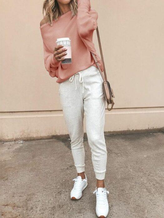 Chica usando una blusa rosa, chandal color beige y tenis blancos