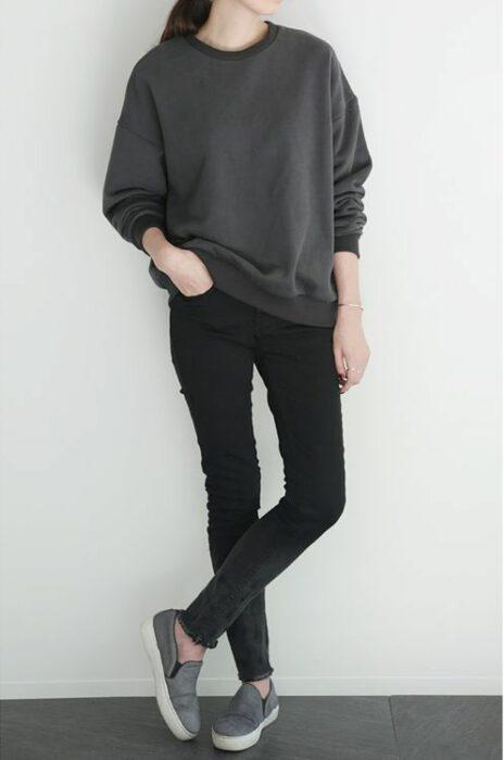 Chica usando sudadera gris holgada, jeans negros y tenis grises