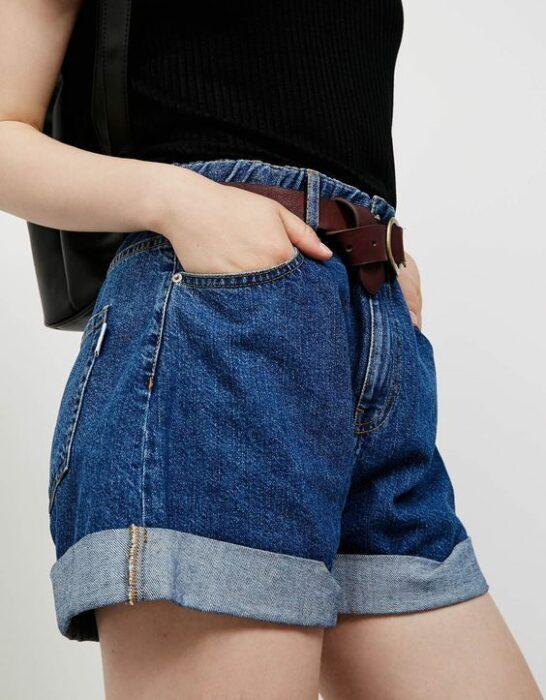 Chica usando blusa negra, shorts de mezclilla holgados con cinturón café