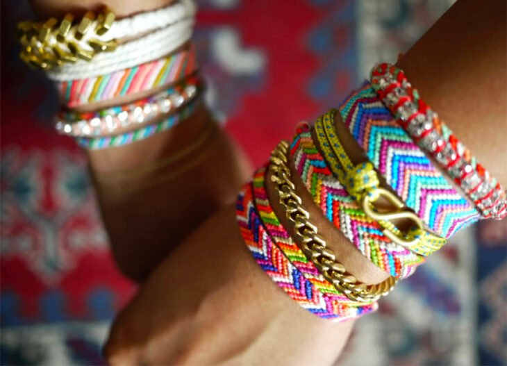 Girl wearing different colored woven bracelets