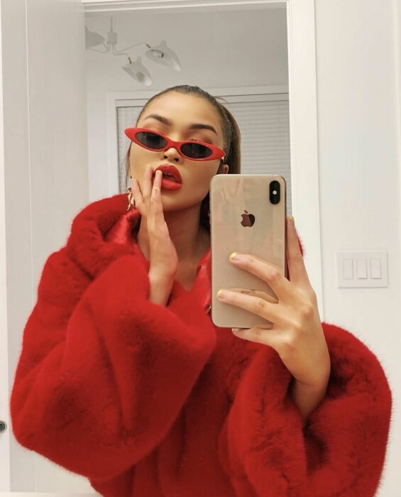 Girl taking a selfie while wearing a red outfit and red with black glasses